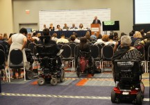 Several people sit in the audience with their mobility devices