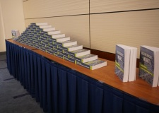 A large stack of books by NeighborWorks America on a table