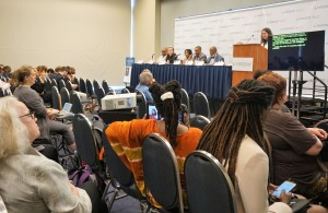 A woman sits in a crowded room, typing into a stenography machine while the panelists speak