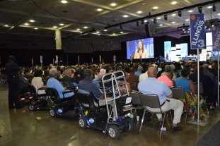 A crowd shot, featuring several scooters and walkers parked in the back of the room
