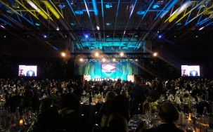A very large room with many people, dimmed lights, and a bright stage with many overhead monitors showing images and captions