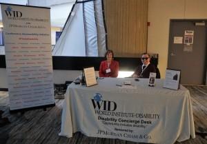 Two WID staff members site behind a desk