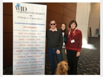Three people and one service dog stand in front of a banner that lists numerous ADA-covered disabilities