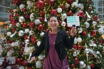 "A woman stands in front of a Christmas tree and holds a whiteboard that says, "" #Nothing about us without us """