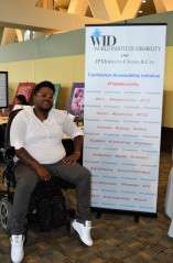 A man in an electric wheelchair poses in front of the This Is Disability sign