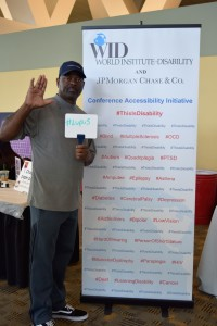 "A man holds up one hand, palm out, and stands in front of the This Is Disability sign; in his free hand, he holds a whiteboard that says, "" #Lupus """