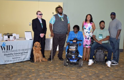 A group of six people with varied disabilities and one service dog stand in front of the Disability Concierge Desk
