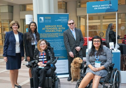 A group of five people with varied disabilities and one service dog stand in front of the Disability Concierge Desk