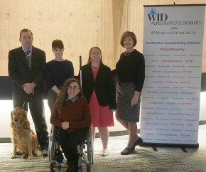 A group of five people with varied disabilities and one service dog pose