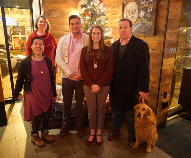 A group of five people with varied disabilities and one service dog pose in front of a Christmas tree
