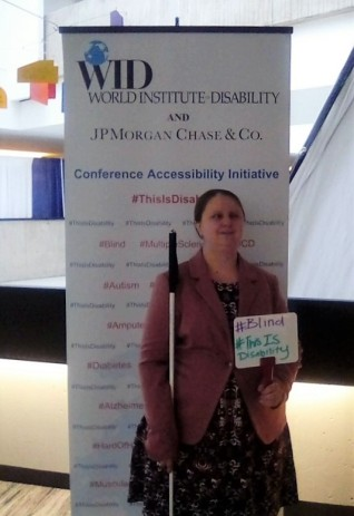 "A woman with a white cane stands in front of the This Is Disabilitiy sign and holds a whiteboard that says, "" #Blind #This Is Disability """