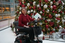 "A woman sits in a scooter in front of a Christmas tree and holds a whiteboard that says, "" #Chronic Illness """