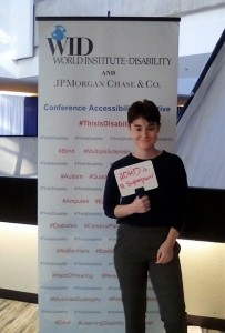 "A woman stands in front of the This Is Disabilitiy sign and holds a whiteboard that says, "" #ADHD is a superpower """