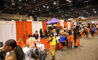 A large expo hall with many people; focus on two disability booths
