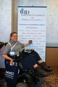 "A woman in a wheelchair sits in front of the This Is Disability sign and gestures to the word ""quadriplegia"" with her coffee cup"