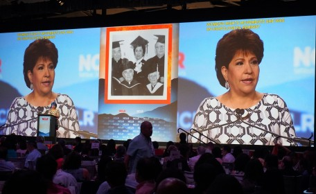 A woman speaks to the audience with captions on the two large screens above her
