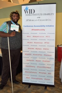 """A man with a white cane stands in front of the This Is Disability sign and holds a whiteboard that says, """" #Blind """""""