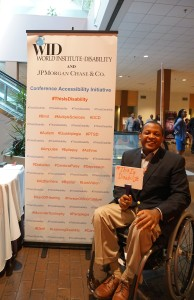 "A man in a wheelchair poses in front of the This Is Disability sign and holds a whiteboard that says, "" #This Is Disability """
