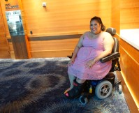 A woman in a pink dress with a cast on one leg sits in an electric wheelchiar