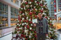 "A man stands in front of a Christmas tree and holds a whiteboard that says, "" #Mental Health Matters """