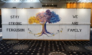 """A large wooden wall, painted with a tree and the words """"Stay strong, Feruson"""" and """"We are family"""""""