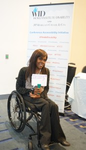 """A woman in a wheelchair poses in front of the This Is Disabilitiy sign and holds a whiteboard that says, """" #Woman with a Disability """""""
