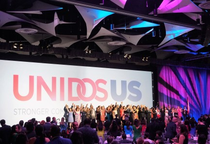 "A large group of people on stage grasp hands and hold them high in the air while ""Unidos US"" shows in large letters on the screen behind them"