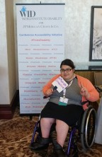 "A woman in a wheelchair sits in front of the This Is Disability sign and holds a whiteboard that says ""multiple disabilities"""
