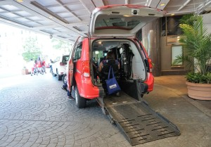 A red van with its trunk open and a wheelchair accessible ramp laid out