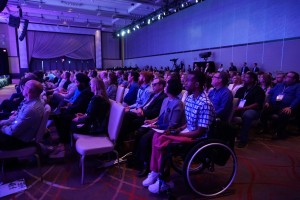 A crowded audience, including the four Disability Ambassadors sitting together