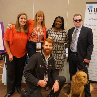 Five people and one service dog pose in front of the Disability Concierge Desk