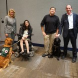 Four people and two service dogs pose together