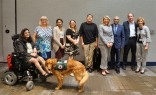 Nine people and two service dogs pose together