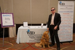 One WID staff member and his service dog pose in front of the Disability Concierge Desk