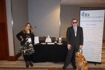 Two people and one service dog stand in front of the Disability Concierge Desk