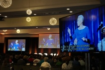 A woman in blue shows up on several screens with captions below her