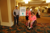 """Two people stand and one person sits in her wheelchair near a sign that says, """"Florida Housing Coalition"""""""