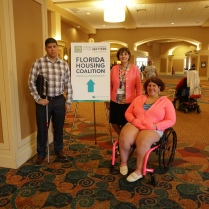 "Two people stand and one person sits in her wheelchair near a sign that says, ""Florida Housing Coalition"""