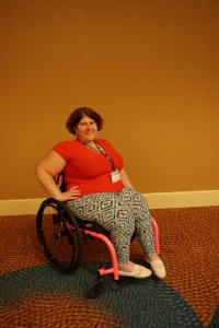 A woman in a wheelchair poses in front of a mustard colored wall