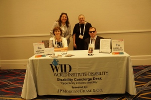Four people pose behind the Disability Concierge Desk