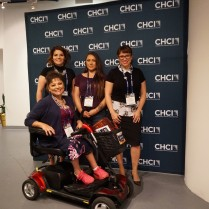 Three women stand and one sits in an electric scooter in front of a CHCI photo-op