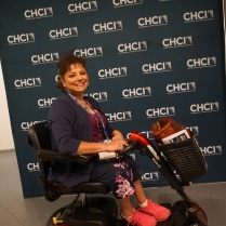 A woman sits in an electric scooter in front of a CHCI photo-op