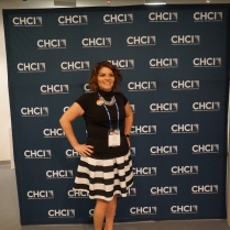 A woman stands in front of a CHCI photo-op