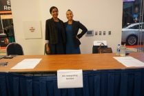 """Two women stand behind a desk with a sign that says, """"ASL Interpreting Services"""""""