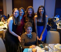 A group of five women in evening dresses pose around a dinner table