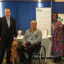 A group of three people with varied disabilities and one service dog pose in front of the Disability Concierge Desk