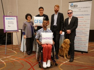 """Five people and one service dog pose with pillows that say """"CFSI"""" and """"EMERGE"""" in front of the Disability Concierge Desk"""