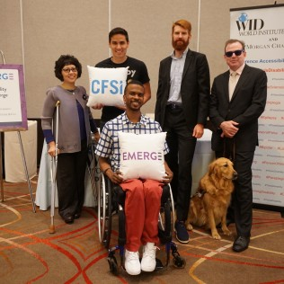 "Five people and one service dog pose with pillows that say ""CFSI"" and ""EMERGE"" in front of the Disability Concierge Desk"