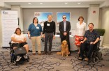 Six people and one service dog pose in front of the Disability Concierge Desk