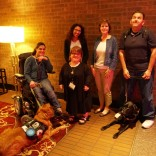 Five people and two service dogs pose against a brick wall